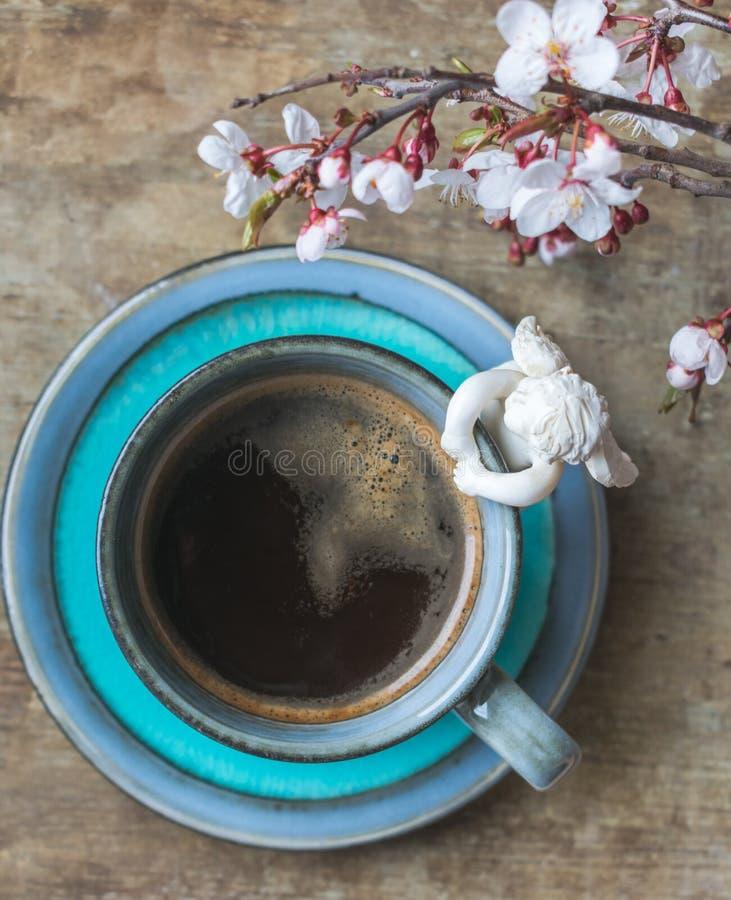 一杯蓝色葡萄酒咖啡的顶视图与天使小雕象和春天树枝的在木背景 图库摄影