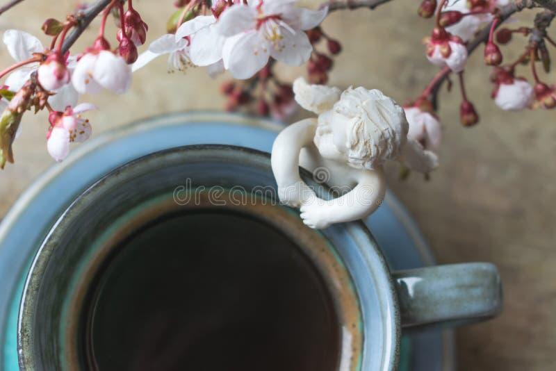 一杯蓝色葡萄酒咖啡的顶视图与天使小雕象和春天树枝的在木背景 库存照片
