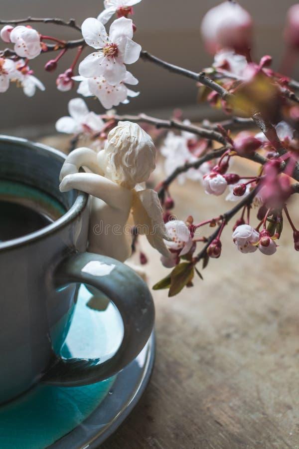 一杯蓝色葡萄酒咖啡的顶视图与天使小雕象和春天树枝的在木背景 免版税库存照片
