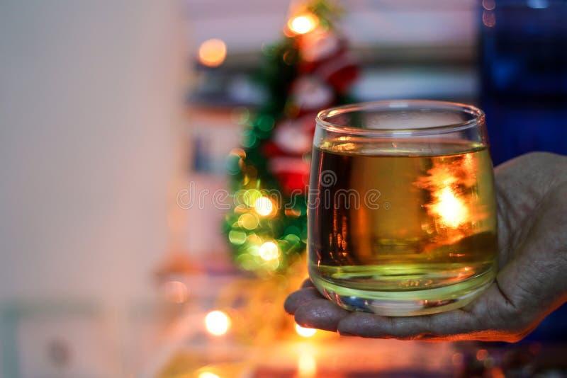 一杯酒精兰姆酒举行有背景在手中弄脏了bokeh光 免版税库存图片
