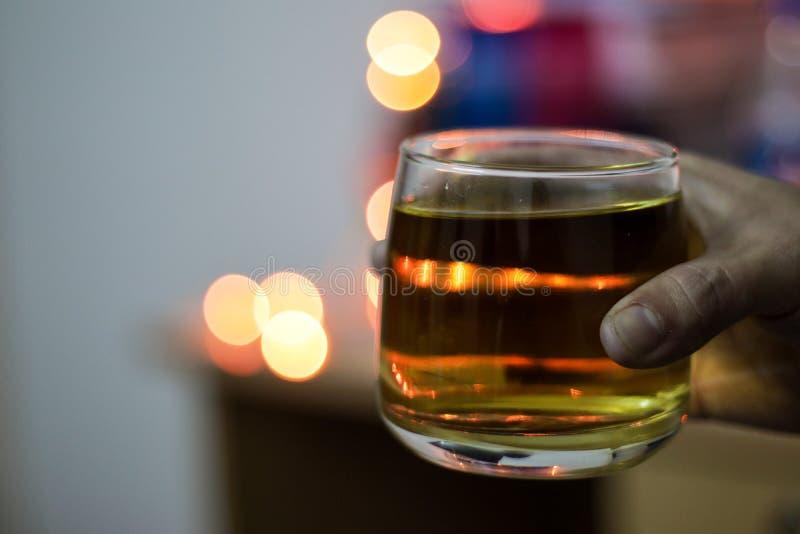 一杯酒精威士忌酒在手中举行与背景迷离bokeh光 免版税库存照片