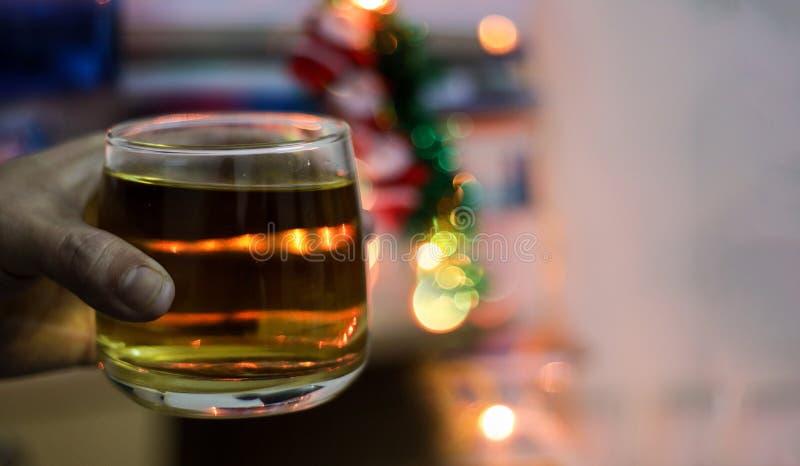一杯酒精威士忌酒在手中举行与背景迷离bokeh光 库存图片