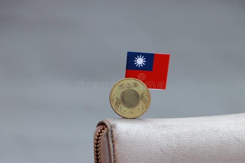一枚五十元硬币在背面,灰色背景皮钱包上的迷你台湾旗杆 免版税库存照片