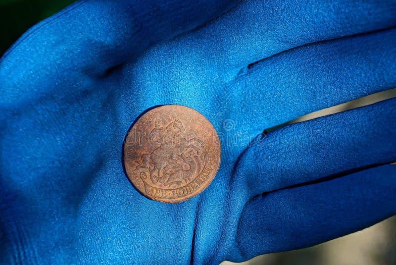 一枚大老铜币在一只手的棕榈说谎在一副蓝色手套的 库存照片