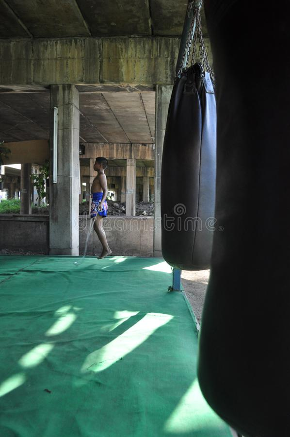 一架年轻泰国泰拳战斗机跳跃绳子在一间把装箱的健身房在一座桥梁下在Minburi,泰国 免版税库存图片