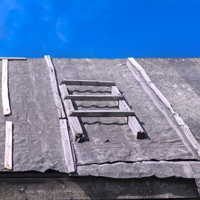 一架木梯子的部分在用防水的焦油纸盖的谷仓屋顶的反对夏天天空蔚蓝 屋顶修理, 库存照片
