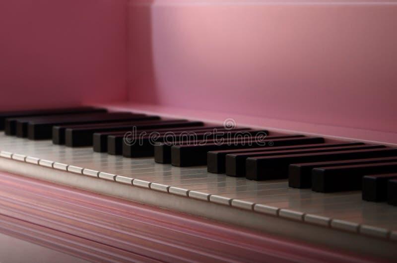 一架桃红色钢琴的键盘的特写镜头 套白色和黑按钮 库存图片