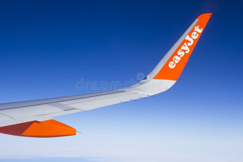 一架空中客车A320商业班机的翼和小翅膀有公司商标的,当在飞行中时 免版税库存图片
