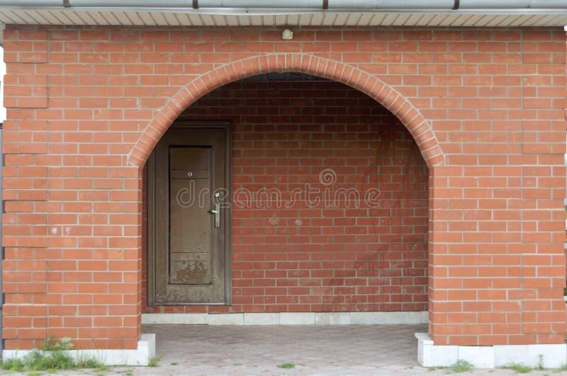 一栋位于红色拱砖墙上的棕色门上,建有鹅卵石入口的乡村老宅 图库摄影
