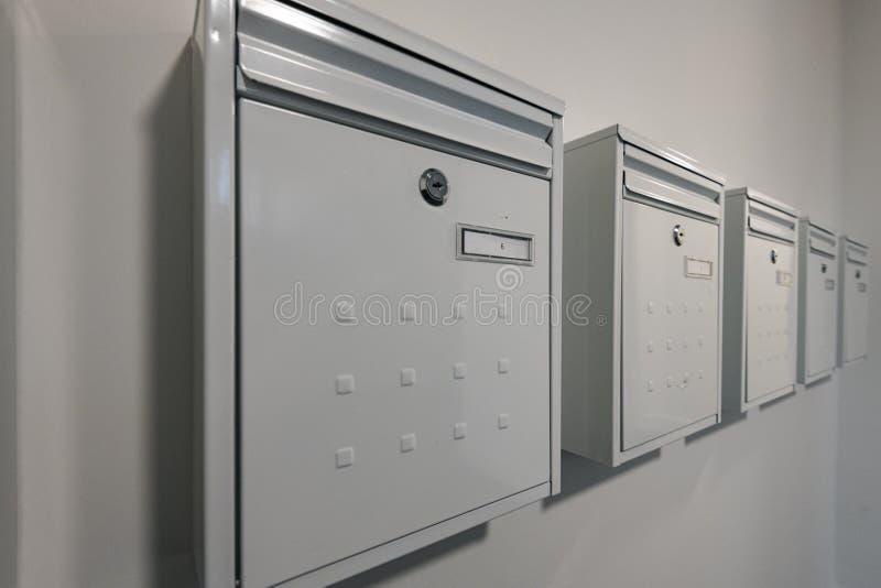 一栋公寓的现代白色金属邮件箱子连续对有数字的白色被绘的墙壁在他们和锁 免版税图库摄影