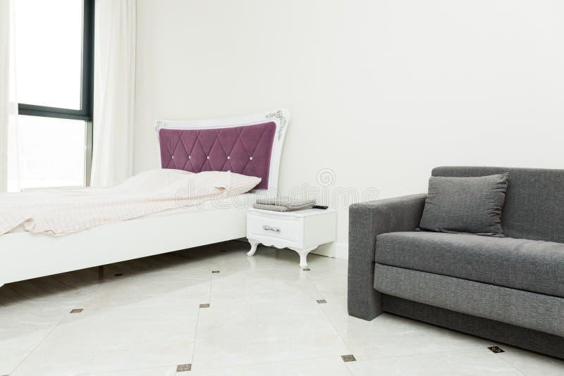 一栋现代公寓的内部在一个明亮的斯堪的纳维亚样式的与颜色口音、沙发和床 库存照片