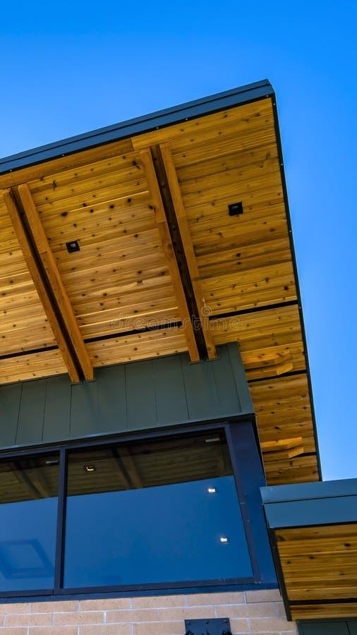 一栋砖瓦房的垂直的框架外部有大玻璃窗和屋顶平台的看法 免版税库存照片