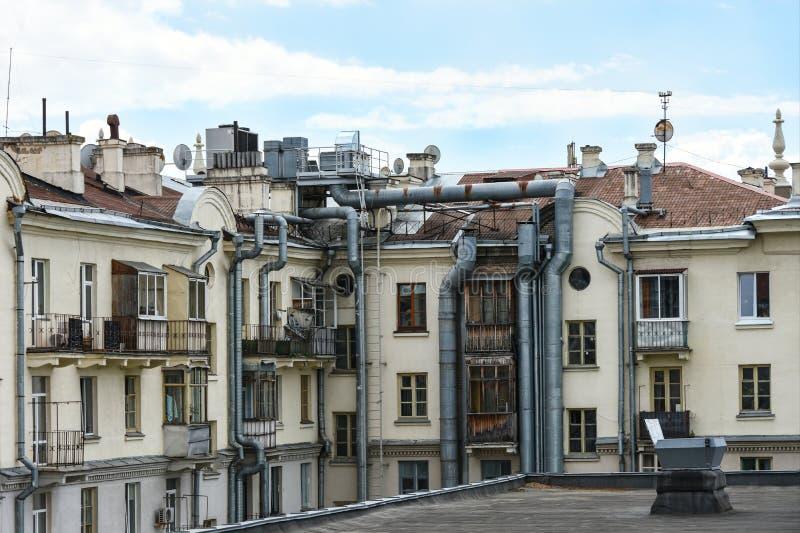 一栋老居民住房的墙壁在有缚住和空调系统的大管子的城市从咖啡馆的 库存照片