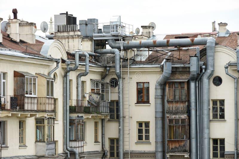 一栋老居民住房的墙壁在有缚住的和适应的系统的大管子的城市从咖啡馆的 免版税库存照片