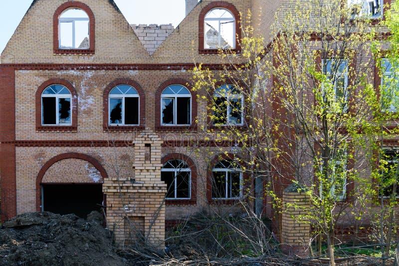 一栋被毁坏的砖瓦房的门面与残破的Windows的 免版税库存照片