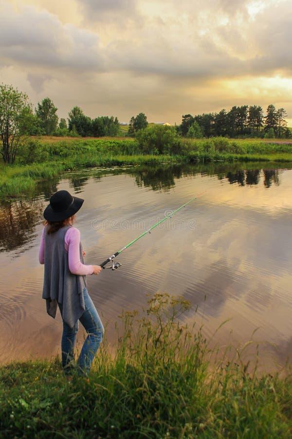 一根帽子钓鱼竿的女孩在湖,夏天风景,在天空的暴风云 o o 免版税库存图片