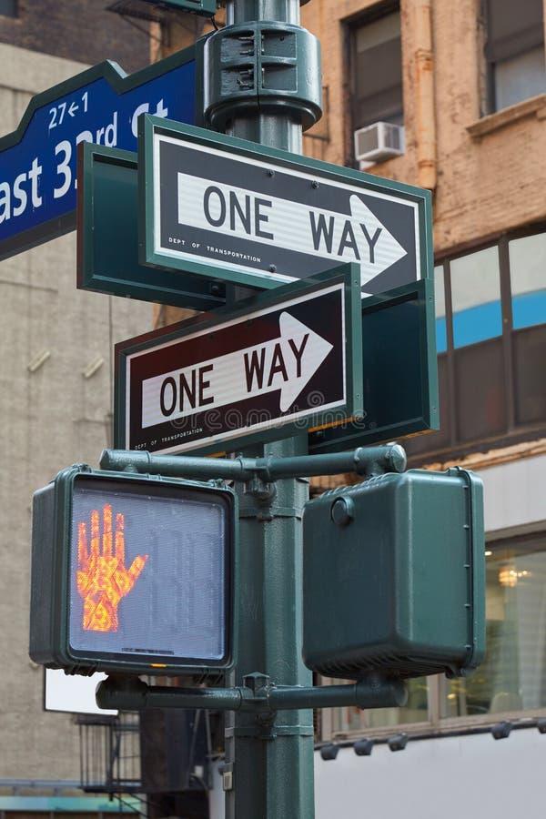 一根方式路牌杆在有红色红绿灯的纽约 图库摄影