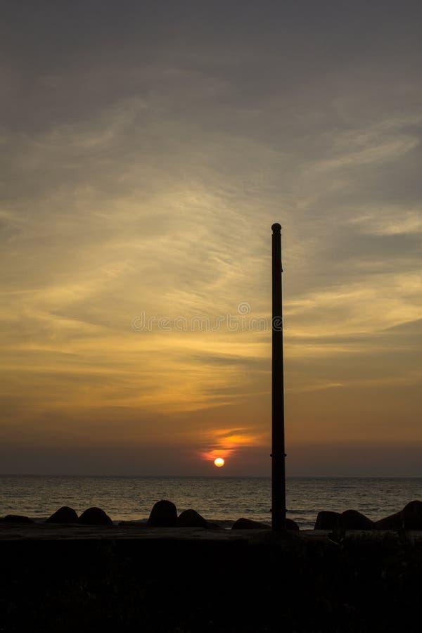 一根柱子的一个黑剪影以海洋为背景的和与太阳和白色的蓝色紫色桃红色黄色日落天空 免版税库存图片