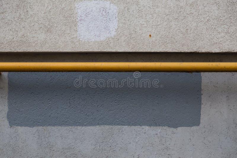 一根水平的煤气管绘与黄色油漆在大厦墙壁旁边 混凝土纹理 灰色油漆长方形  免版税图库摄影