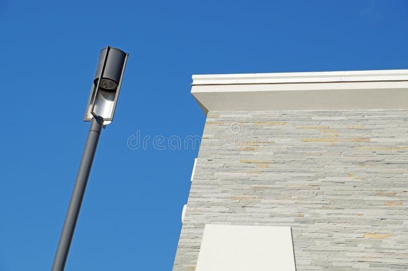 一根现代白色金属街道路灯柱的特写镜头有五个灯笼的反对清楚的蓝天 复制空间 图库摄影
