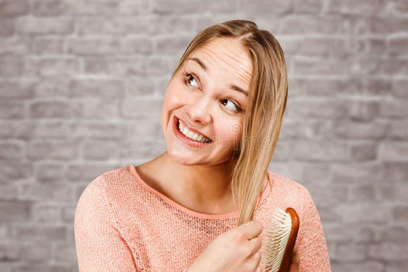 一根美丽的微笑的年轻女人梳子头发的画象,在砖墙背景 免版税库存照片