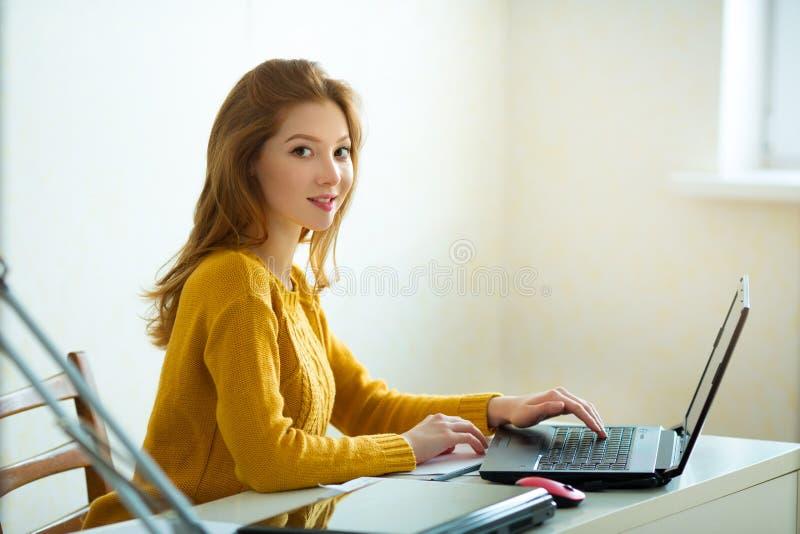 一根黄色毛线衣和红色头发的美丽的女孩 免版税库存照片