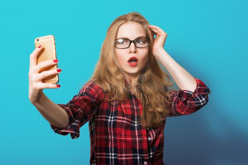 一格子衬衫的白肤金发的女孩有电话的 妇女戴着眼镜的画象 与智能手机的行家画象 免版税库存图片