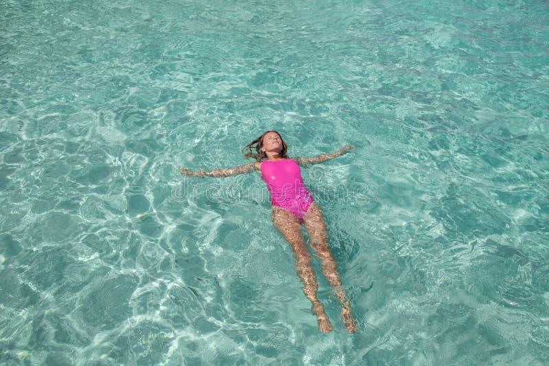 一桃红色泳装放松的美女 图库摄影