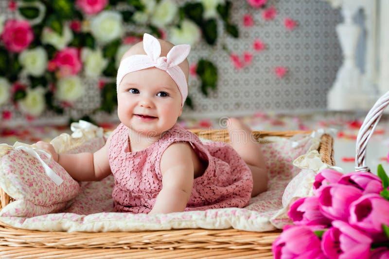 一桃红色礼服lyin的小非常逗人喜爱的吃惊的微笑的女婴 免版税库存照片