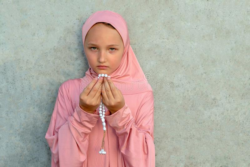 一桃红色hijab的一个孩子与小珠在他的有拷贝空间的手上 人宗教生活方式概念 图库摄影