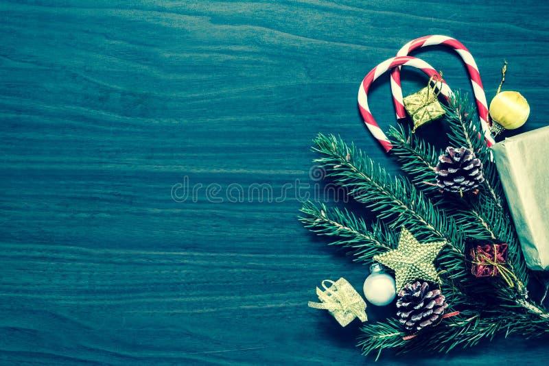 一棵圣诞树的分支与球的,冷杉球果、传统糖果和箱子有礼物的wodden背景 免版税库存图片
