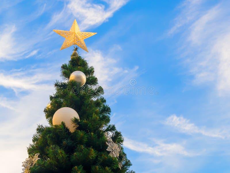 一棵圣诞树的特写镜头反对一天空蔚蓝的与白色云彩 用金星和银色球装饰的圣诞树,拷贝 免版税库存图片