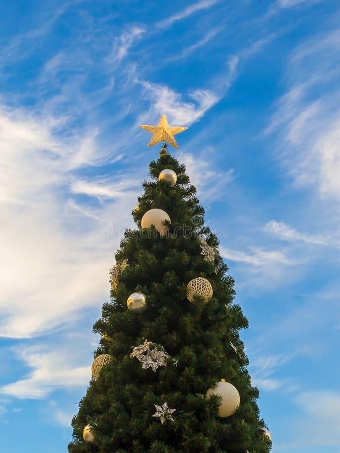 一棵圣诞树的特写镜头反对一天空蔚蓝的与白色云彩 用金星和银色球装饰的圣诞树 图库摄影