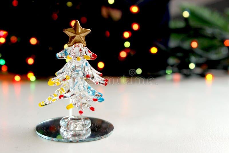 一棵小纪念品圣诞树由玻璃制成在闪烁圣诞灯背景, bokeh作用 库存图片
