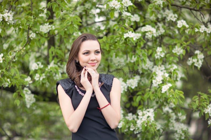 一棵开花的树的背景的女孩 免版税库存图片