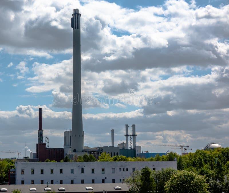 一棵结合热能和动能植物的看法有一个长的烟囱的在用云彩盖的剧烈的天空前面 免版税库存照片