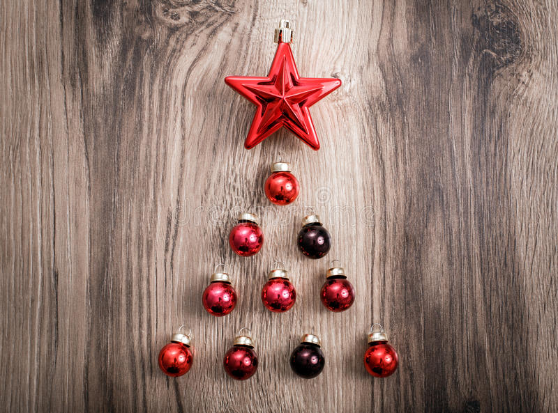 以一棵Xmas树的形式红色圣诞节装饰品在土气木背景 圣诞快乐看板卡 新年好 顶视图 免版税库存照片