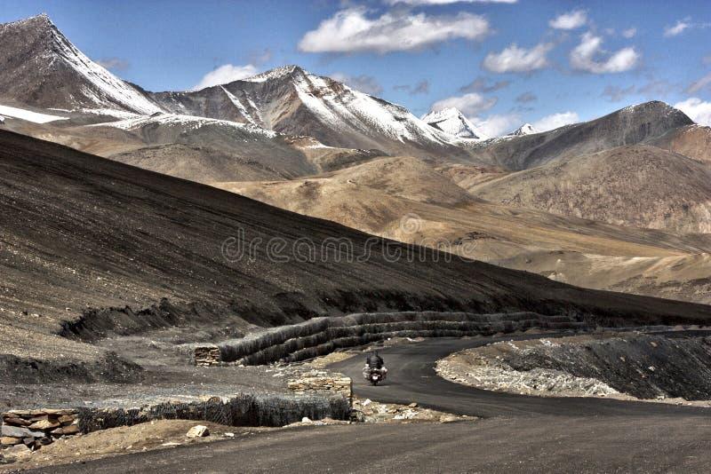 一次冒险旅行的一个骑自行车的人在深深一条路在拉达克里面,印度谷  免版税图库摄影