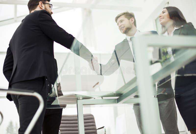 一次可靠的合作的概念:商务伙伴握手工作场所的背景的 库存图片