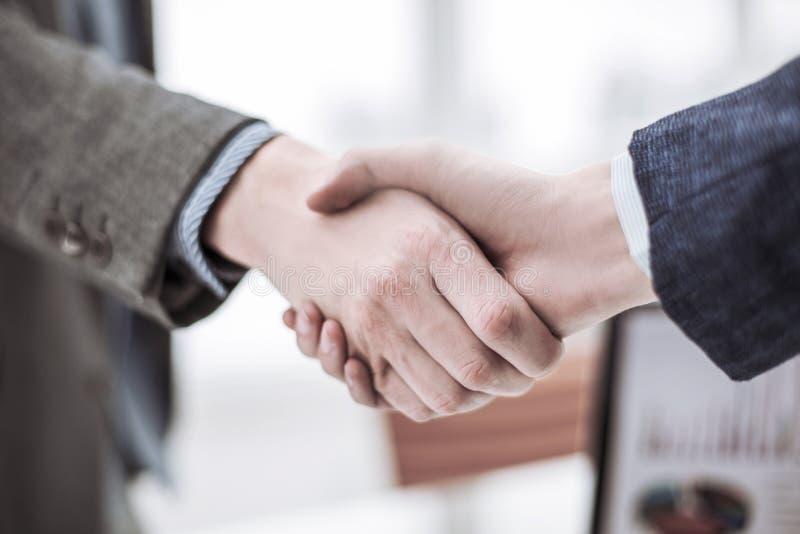 一次可靠的合作的概念:商务伙伴握手被弄脏的轻的背景的 库存图片