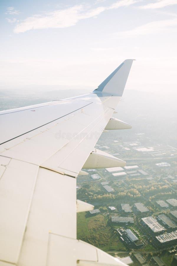一次大商用飞机飞行的翼在一个城市的在美国 库存图片