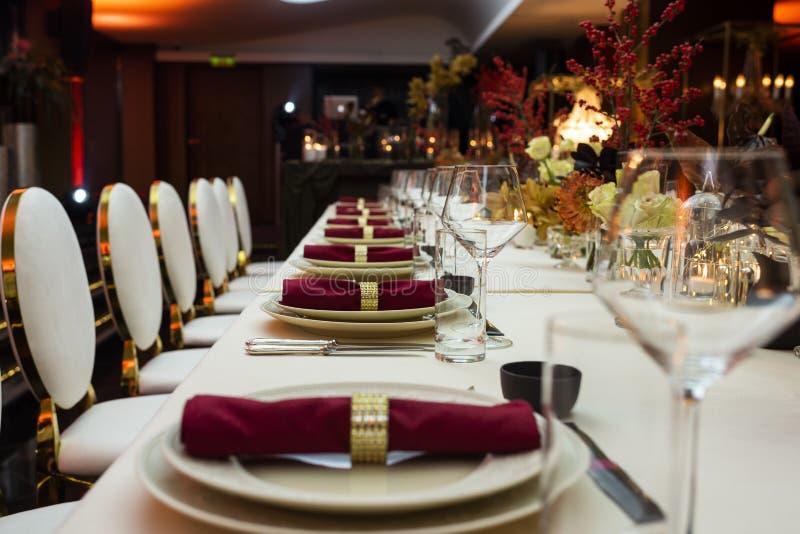 一次大庆祝的装饰的桌在晚上在用花和蜡烛装饰的餐馆 免版税库存照片