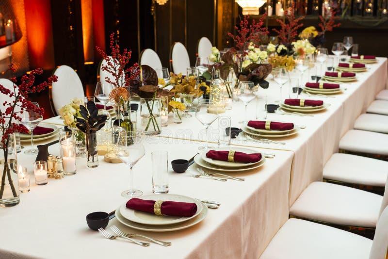 一次大庆祝的装饰的桌在晚上在用花和蜡烛装饰的餐馆 库存图片