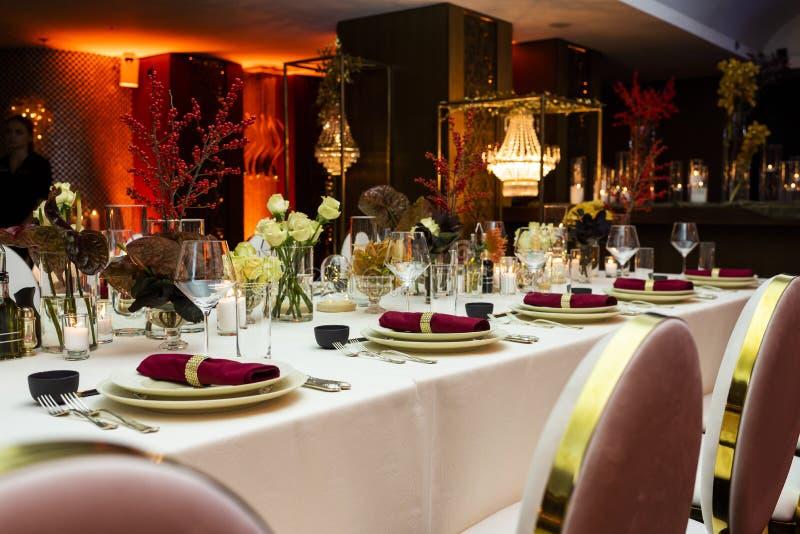 一次大庆祝的装饰的桌在晚上在用花和蜡烛装饰的餐馆 库存照片