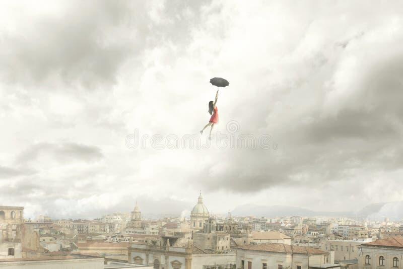 一次妇女飞行的超现实的片刻与她的伞的在城市 免版税库存图片