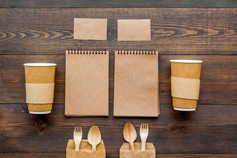 一次性事 碗筷和笔记本在木背景顶视图 免版税库存图片