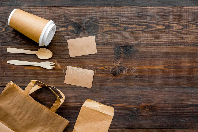 一次性事 纸袋,在木背景顶视图拷贝空间的碗筷 免版税库存图片