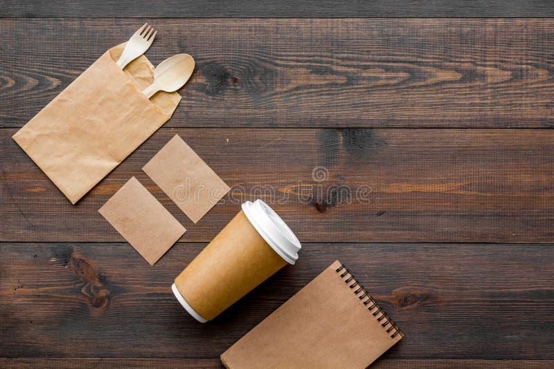一次性事 纸袋,碗筷,在木背景顶视图拷贝空间的笔记本 免版税库存图片
