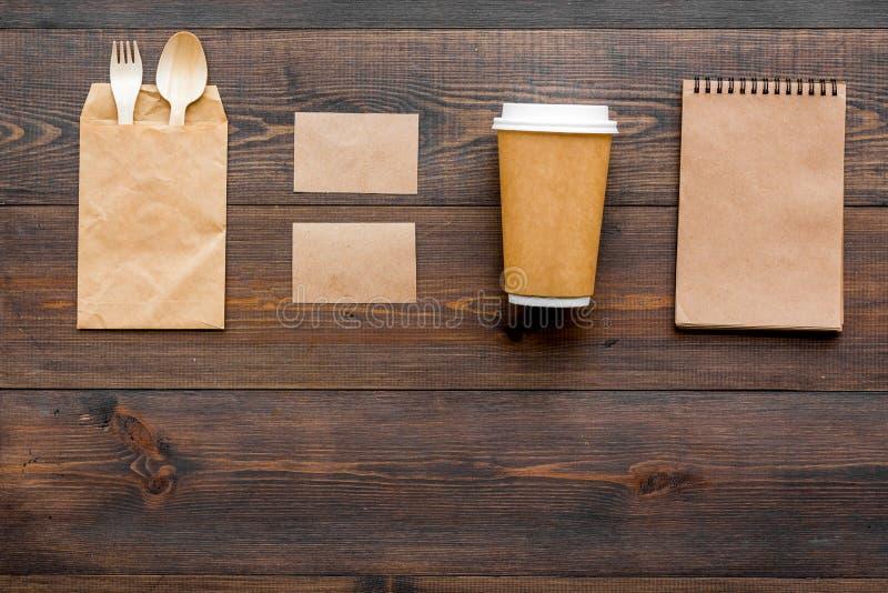 一次性事 纸袋,碗筷,在木背景顶视图copyspace的笔记本 免版税库存照片