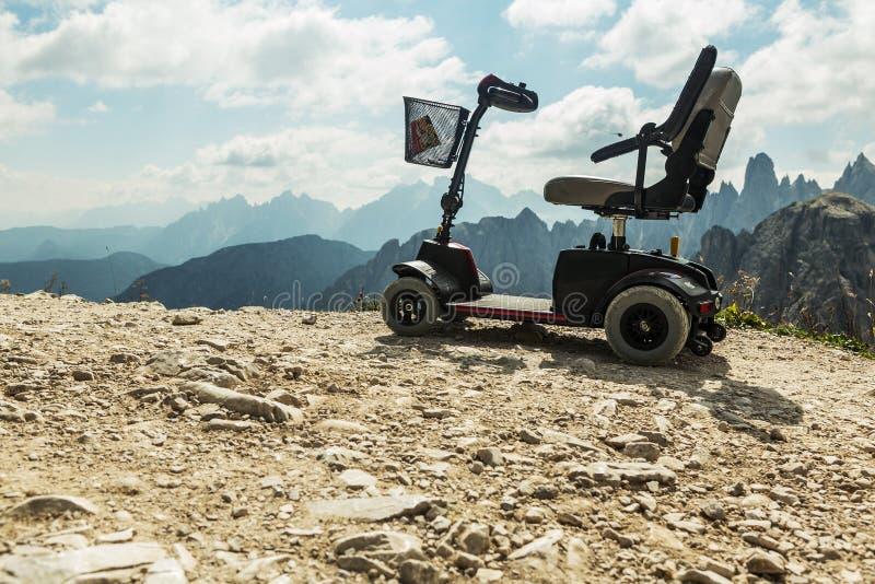 一次性人民的,在山的流动电儿童车,白云岩,意大利动力化的轮椅 免版税图库摄影
